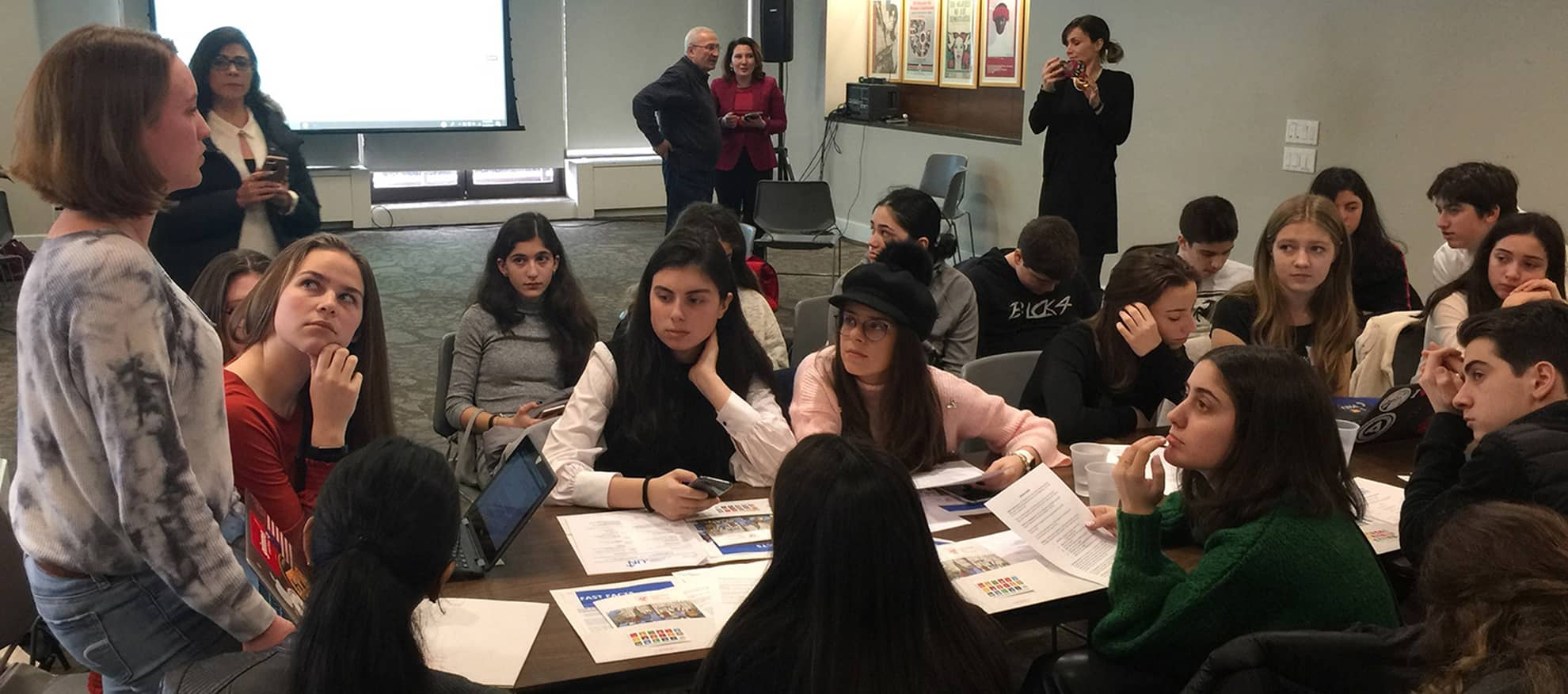 Lilian Oxley (standing) helps guide discussion among students from Mexico, the Republic of Georgia, New York and New Jersey on the subtheme: Science-based facts and predictions related to climate change. In the background are teachers from these schools, who are there to observe but not intervene.